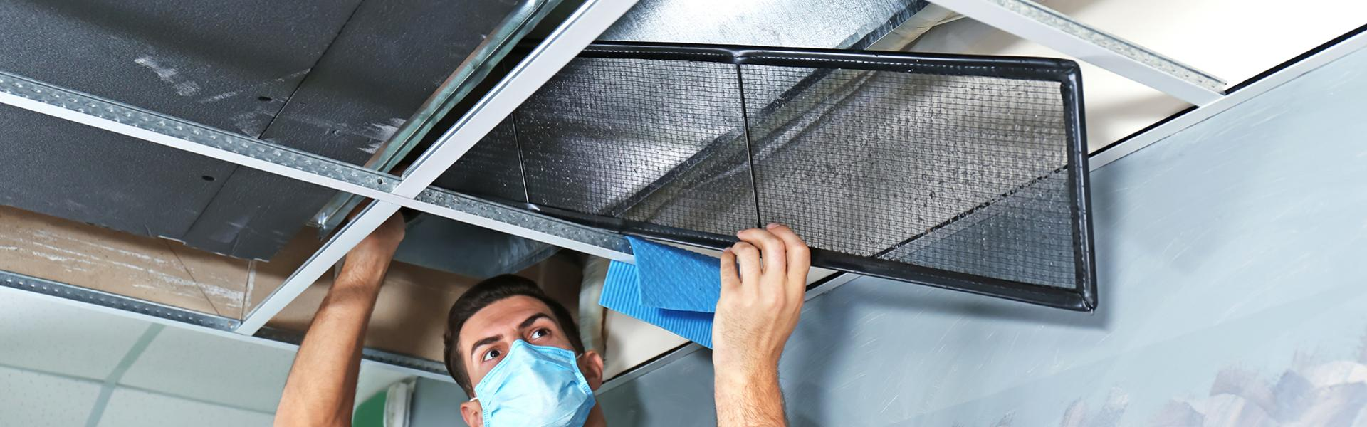 Professional cleaner cleaning out a false ceiling